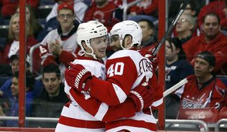 Detroit Red Wings center Gustav Nyquist (14), from Sweden, and left wing Henrik Zetterberg (40), also from Sweden, celebrate Nyquist's goal in the second period of an NHL hockey game against the Washington Capitals, Sunday, Feb. 2, 2014, in Washington. (AP Photo/Alex Brandon)
