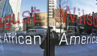 This photo made with a fisheye lens on Thursday, Jan. 30, 2014, shows buildings and traffic along Liberty Ave. in Pittsburgh that are reflected in the windows with the signage for the August Wilson Center for African American Culture. The center may soon be sold to pay off millions in debt, and some experts say it's a telling reflection on the difficulties of promoting theatre and black culture in America. (AP Photo/Keith Srakocic)