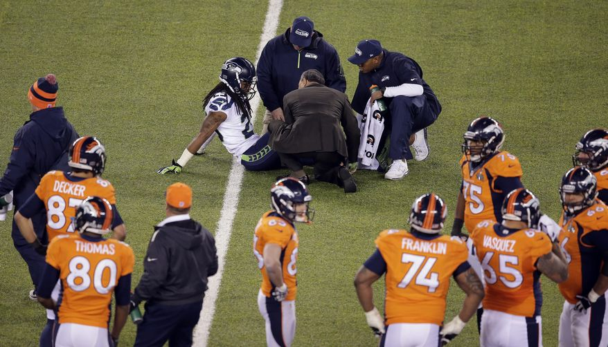 Seattle Seahawks' Richard Sherman is attended to by medical staff due to injury against the Denver Broncos during the second half of the NFL Super Bowl XLVIII football game Sunday, Feb. 2, 2014, in East Rutherford, N.J. (AP Photo/Charlie Riedel)
