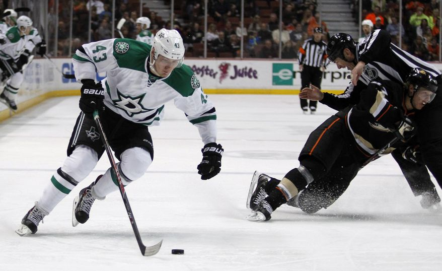 Dallas Stars right wing Valeri Nichushkin (43), of Russia controls the puck as Anaheim Ducks defenseman Hampus Lindholm, right, of Sweden collides into linesman Pierre Racicot in the first period of an NHL hockey game Saturday, Feb. 1, 2014, in Anaheim, Calif. (AP Photo/Alex Gallardo)