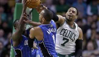 Boston Celtics center Jared Sullinger (7) grapples with Orlando Magic guard Victor Oladipo, behind left, and guard Arron Afflalo, center, for control of the ball in the third quarter of an NBA basketball game on Sunday, Feb. 2, 2014, in Boston. The Celtics won 96-89. (AP Photo/Steven Senne)