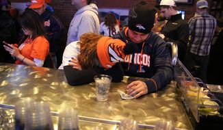 Denver Broncos fans Tatiana Bohorquez and Jorge Puerto look away from the TV while watching their team  fall behind the Seattle Seahawks during the second half of the Super Bowl, inside Jackson's, a sports bar and grill in Denver, Sunday, Feb. 2, 2014. The  Seahawks won 43-8. (AP Photo/Brennan Linsley) **FILE**