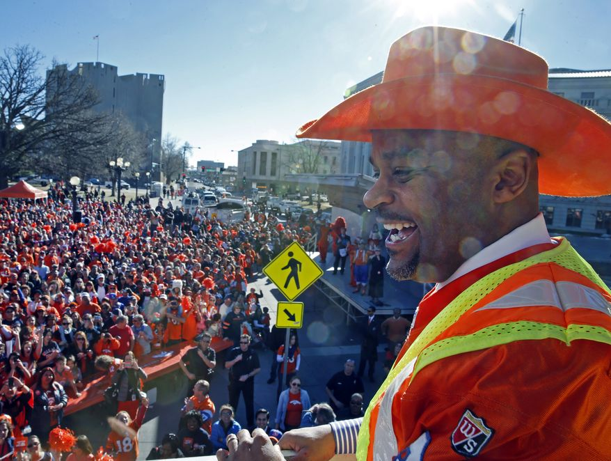 Denver Mayor Michael Hancock smiles as he looks out over a crowd of Denver Broncos fans cheering for the Broncos at a rally in Denver, Friday, Jan. 17, 2014. The Broncos are scheduled to host the New England Patriots on Sunday for the AFC championship NFL football game. (AP Photo/Brennan Linsley)