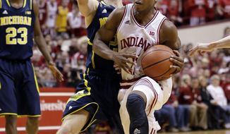 Indiana guard Yogi Ferrell, right, drives against Michigan guard Spike Albrecht in the second half of an NCAA college basketball game in Bloomington, Ind., Sunday, Feb. 2, 2014. Indiana defeated Michigan 63-52. (AP Photo/Michael Conroy)