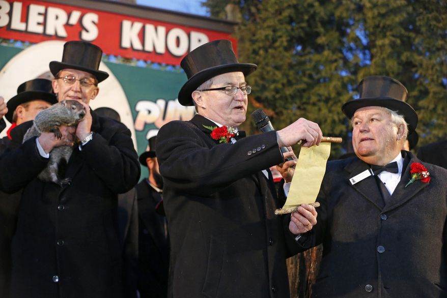 Punxsutawney Phil is held by Ron Ploucha, left, as Ground Club Vice President Jeff Lundy, center, reads the weather proclamation after Phil saw his shadow and predicted six more weeks of winter weather after, as Ground Club President, Bill Deeley, right, listens on Gobblers Knob in Punxsutawney, Pa.,  Sunday, Feb. 2, 2014.  (AP Photo/Gene J. Puskar)