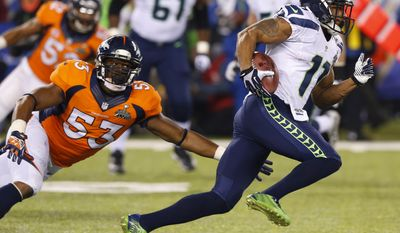 Seattle Seahawks' Percy Harvin sprints past Denver Broncos' Steven Johnson after an interception during the second half of the NFL Super Bowl XLVIII football game Sunday, Feb. 2, 2014, in East Rutherford, N.J. (AP Photo/Paul Sancya)