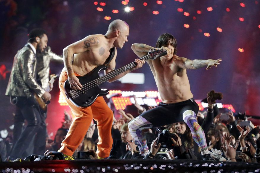 The Red Hot Chili Peppers band members Flea, center, and Anthony Kiedis perform during the halftime show of the NFL Super Bowl XLVIII football game Sunday, Feb. 2, 2014, in East Rutherford, N.J. (AP Photo/Julio Cortez)