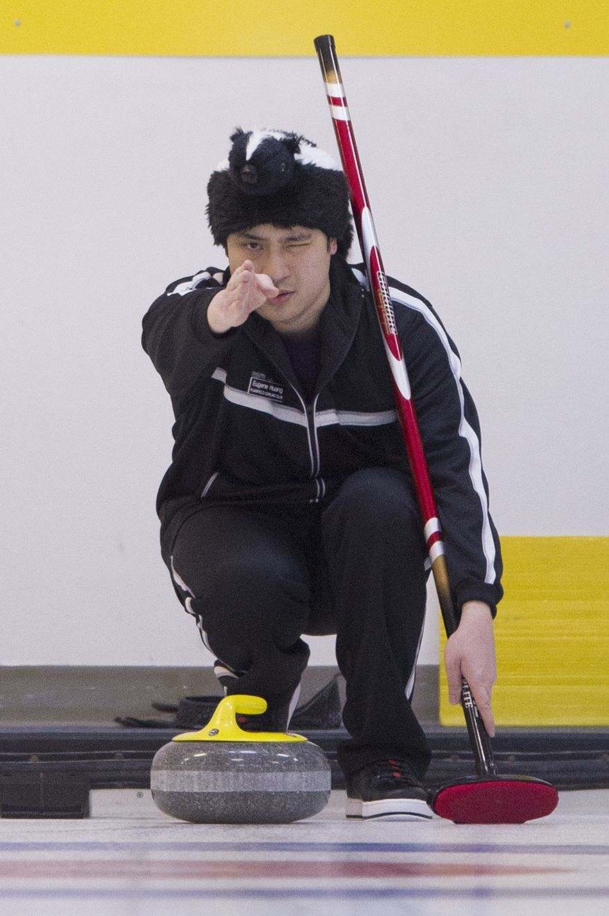 Eugene Huang from the Plainfield Curling Club, N.J., lines up his delivery  during the curling competition at the Potomac Curling Club in Laurel, Md. (Preston Keres/Special to The Washington Times)