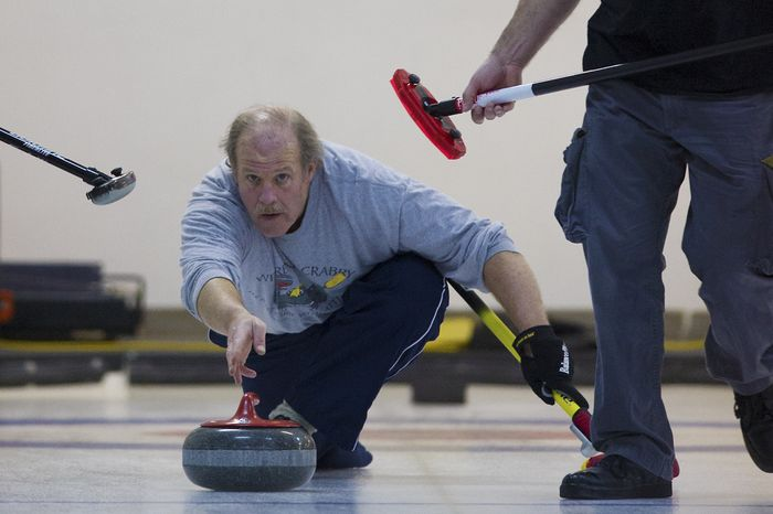 George Shirk, from the Potomac Curling Club, Md., delivers the stone down the sheet  during the curling competition at the Potomac Curling Club in Laurel, Md. (Preston Keres/Special to The Washington Times)