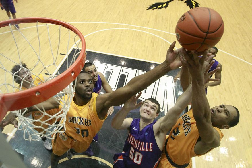 Wichita State's Tekele Cotton, right, and Kadeem Coleby, left, battle Evansville's Blake Simmons for a rebound during the second half of an NCAA college basketball game in Wichita, Kan., Saturday, Feb. 1, 2014. (AP Photo/The Wichita Eagle, Travis Heying) LOCAL TV OUT; MAGAZINES OUT; LOCAL RADIO OUT; LOCAL INTERNET OUT