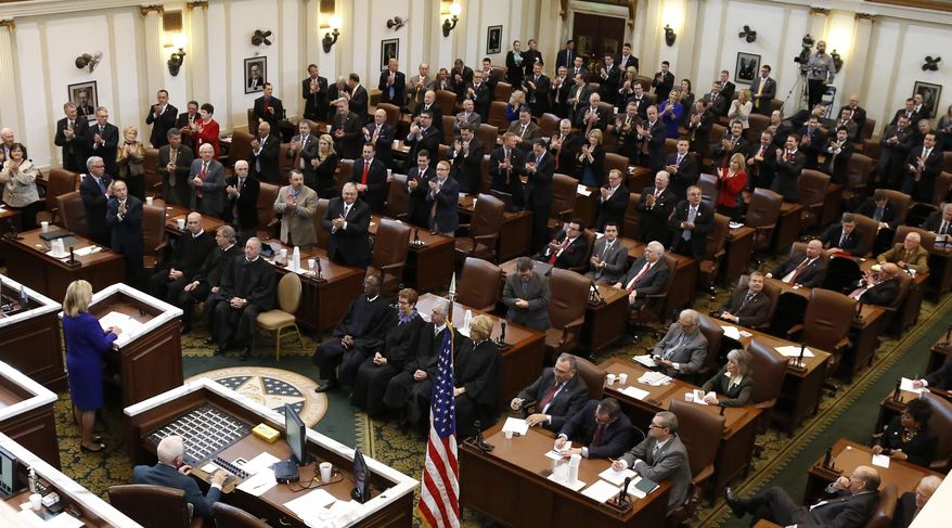 Members of the Oklahoma Legislature applaud as Oklahoma Governor Mary Fallin, left, gives her State of the State address in Oklahoma City, Monday, Feb. 3, 2014. (AP Photo/Sue Ogrocki)