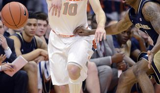 Syracuse's Trevor Cooney passes against Notre Dame's Eric Atkins during the first half of an NCAA college basketball game in Syracuse, N.Y., Monday, Feb. 3, 2014. (AP Photo/Kevin Rivoli)