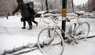 Pedestrians make their way past a snow-covered bicycle as heavy snow falls Monday, Feb. 3, 2014, in New York. After several days of mild weather, snow has returned to the Northeast. (AP Photo/Jason DeCrow)