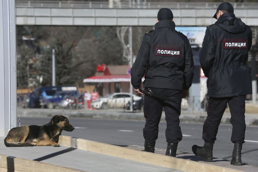 Policemen walk past a stray dog near the Media Center of the 2014 Winter Olympics, Monday, Feb. 3, 2014, in Krasnaya Polyana, Russia.(AP Photo/Dmitry Lovetsky)