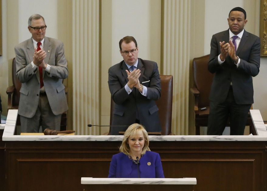 Oklahoma Governor Mary Fallin, bottom, is applauded by President Pro Tempore of the Oklahoma Senate, Brian Bingman, left, R-Sapulpa, Oklahoma Lt. Gov. Todd Lamb, center, and Oklahoma Speaker of the House, T.W. Shannon, right, R-Lawton, during her State of the State address in Oklahoma City, Monday, Feb. 3, 2014. (AP Photo/Sue Ogrocki)