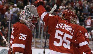 Detroit Red Wings goalie Jimmy Howard (35) is congratulated by defenseman Niklas Kronwall (55) of Sweden after their 2-0 win over the Vancouver Canucks in an NHL hockey game in Detroit, Monday, Feb. 3, 2014. (AP Photo/Carlos Osorio)