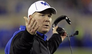 FILE - In this file photo from Nov. 30, 2013, Kentucky coach Nark Stoops questions a call against his team in an NCAA college football game against Tennessee in Lexington, Ky. (AP Photo/Garry Jones, File)