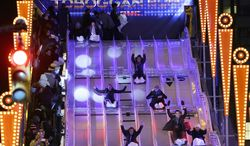 """Fans slide down the toboggan run on """"Super Bowl Boulevard"""" in New York's Times Square, Friday, Jan. 31, 2014. The Seattle Seahawks are scheduled to play the Denver Broncos in NFL football's Super Bowl XLVIII game on Sunday, Feb. 2, in East Rutherford, N.J. (AP Photo/Ben Margot)"""