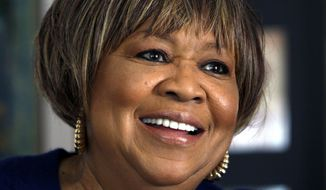 "FILE  - In this Jan. 11, 2011 file photo, Mavis Staples gives an interview with The Associated Press in her Chicago home. The Newport Folk Festival says gospel singer Mavis Staples will perform in this year's line-up. Staples is the first act to be announced for the 2014 festival, which will take place from July 25 to July 27. The festival says special guests will honor her birthday and ""75 Years of Mavis"" throughout the weekend. (AP Photo/Charles Rex Arbogast, File)"