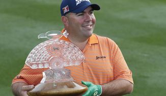 Kevin Stadler smiles as he poses for photographers with the championship trophy after winning the Phoenix Open golf tournament on Sunday, Feb. 2, 2014, in Scottsdale, Ariz. (AP Photo/Ross D. Franklin)