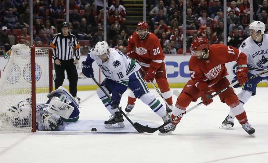 Detroit Red Wings right wing Patrick Eaves (17) shoots the puck towards Vancouver Canucks goalie Eddie Lack during the second period of an NHL hockey game in Detroit, Monday, Feb. 3, 2014. (AP Photo/Carlos Osorio)