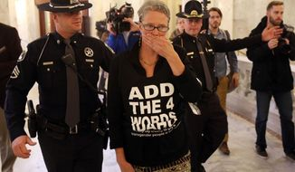 Former Idaho state Sen. Nicole LeFavour is arrested after blocking the entrance of the Senate chambers at the Idaho Statehouse on Monday, Feb. 3, 2014, in Boise, Idaho. She was part of a group of protestors who blocked the entrance while advocating adding gender identity and sexual orientation to the state's human rights ordinance. They cover their mouths to symbolize their feelings of disenfranchisement. (AP Photo/The Idaho Statesman, Joe Jaszewski) LOCAL TV OUT (KTVB 7)