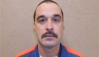 ** FILE ** This Feb. 11, 2013, photo provided by the Michigan Department of Corrections shows Michael David Elliot. Elliot, who is serving life behind bars for murder in four 1993 deaths in Michigan, has escaped from prison and may have abducted a woman before she got away in Indiana, according to officials. (AP Photo/Michigan Department of Corrections)