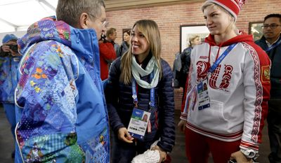 International Olympic Committee President Thomas Bach, left, is greeted by United States speed skater Anna Ringsred, center, and Russia ice hockey player Iya Gavrilova, right, while touring the Coastal Cluster athlete's village at the 2014 Winter Olympics, Tuesday, Feb. 4, 2014, in Sochi, Russia. (AP Photo/David Goldman)