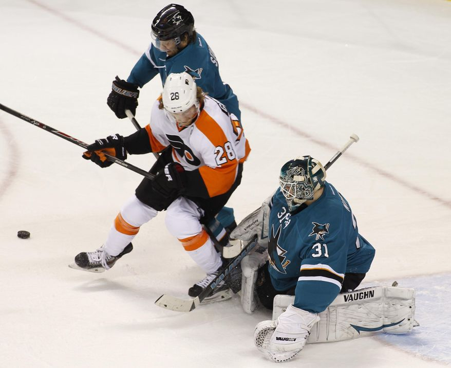 Philadelphia Flyers' Claude Giroux (28) and San Jose Sharks' Brad Stuart struggle for the puck in front of Sharks goalie Antti Niemi (31) during the second period of an NHL hockey game, Monday, Feb. 3, 2014, in San Jose, Calif. (AP Photo/George Nikitin)