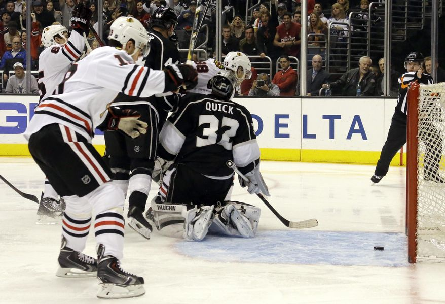 Chicago Blackhawks center Jonathan Toews (19) celebrates a goal by Patrick Kane, not shown, against Los Angeles Kings goalie Jonathan Quick (32) in the first period of an NHL hockey game in Los Angeles, Monday, Feb. 3, 2014. (AP Photo/Reed Saxon)