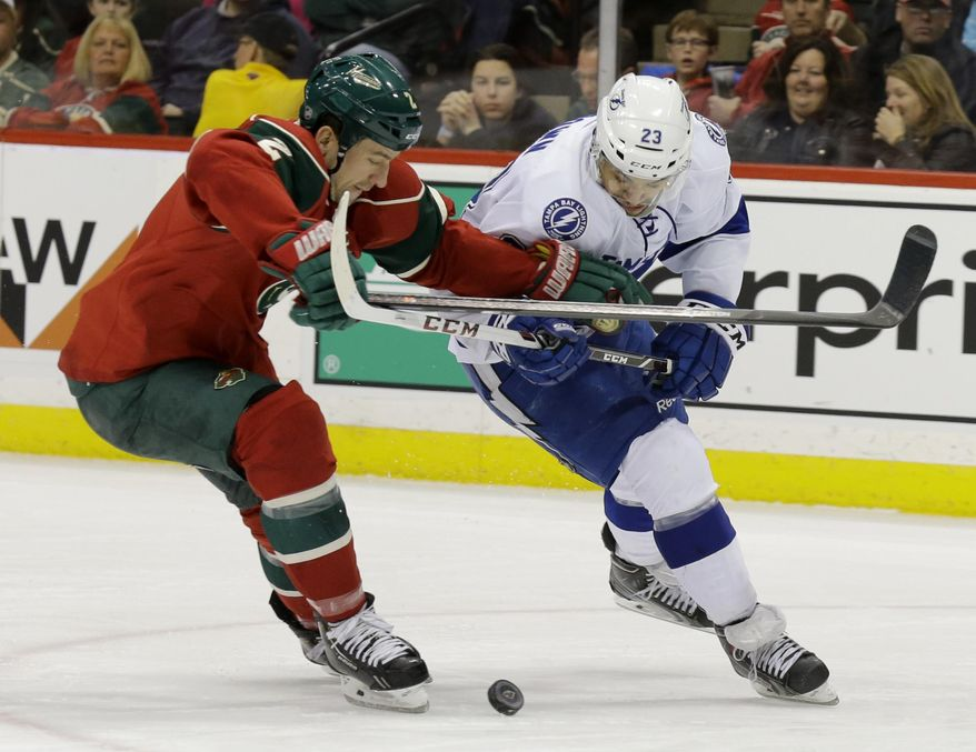 Minnesota Wild defenseman Keith Ballard, left, holds Tampa Bay Lightning right wing J.T. Brown (23) off the puck during the second period of an NHL hockey game in St. Paul, Minn., Tuesday, Feb. 4, 2014. (AP Photo/Ann Heisenfelt)