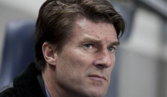 FILE - In this Sunday Dec. 1, 2013 file photo, Swansea City's manager Michael Laudrup takes his seat before his team's 3-0 loss to Manchester City during their English Premier League soccer match at the Etihad Stadium, Manchester, England. Premier League club Swansea fired Michael Laudrup on Tuesday Feb. 4, 2014, with the widely-admired manager paying the price for a slump in the year since winning the League Cup. (AP Photo/Jon Super, File)