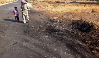** FILE ** In this Wednesday, Nov. 20, 2013, file photo, a man and child walk past a crater from a suicide car bomb attack on the road between the border town of Rafah and the coastal city of el-Arish, Egypt. (AP Photo/Ahmed Abu Deraa, File)