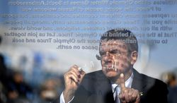 International Olympic Committee President Thomas Bach signs the Olympic truce wall during a ceremony in the Coastal Cluster Olympic Village at the 2014 Winter Olympics, Tuesday, Feb. 4, 2014, in Sochi, Russia. (AP Photo/David Goldman)