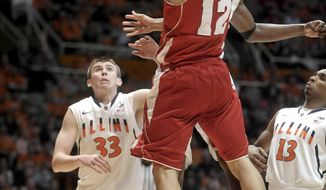 Wisconsin guard Traevon Jackson (12) drives on Illinois' Nnanna Egwu, obscured, during the second half of an NCAA college basketball game Tuesday, Feb. 4, 2014, in Champaign, Ill. (AP Photo/Rick Danzl)