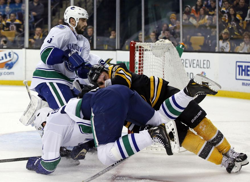 Boston Bruins left wing Brad Marchand, right, crashes with Vancouver Canucks defenseman Alexander Edler, front left, as he tries to score, while Canucks defenseman Jason Garrison (5) watches during the second period of an NHL hockey game in Boston on Tuesday, Feb. 4, 2014. (AP Photo/Elise Amendola)