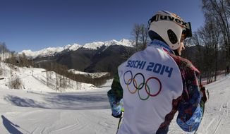 Olympic worker Pavel Dovgiy prepares to ski down the Alpine course ahead of the 2014 Sochi Winter Olympics, Tuesday, Feb. 4, 2014, in Krasnaya Polyana, Russia. (AP Photo/Charles Krupa)