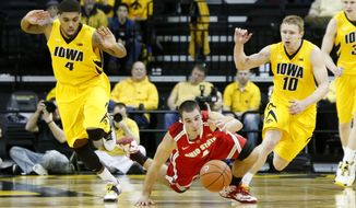 Ohio State guard Aaron Craft (4) drives for the ball between Iowa's Roy Devyn Marble (4) and Mike Gesell (10) during the second half of an NCAA college basketball game at Carver-Hawkeye Arena in Iowa City, Iowa, on Tuesday, Feb. 4, 2014. Ohio State won 76-69. (AP Photo/Cliff Jette)