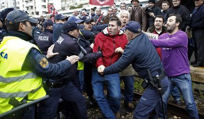 Portuguese railway workers scuffle with Portuguese police officers as the workers block the rail track during a protest at Lisbon's Santa Apolonia train station, Tuesday, Feb. 4, 2014. The protest was against salary cuts and other austerity measures. (AP Photo/Francisco Seco)