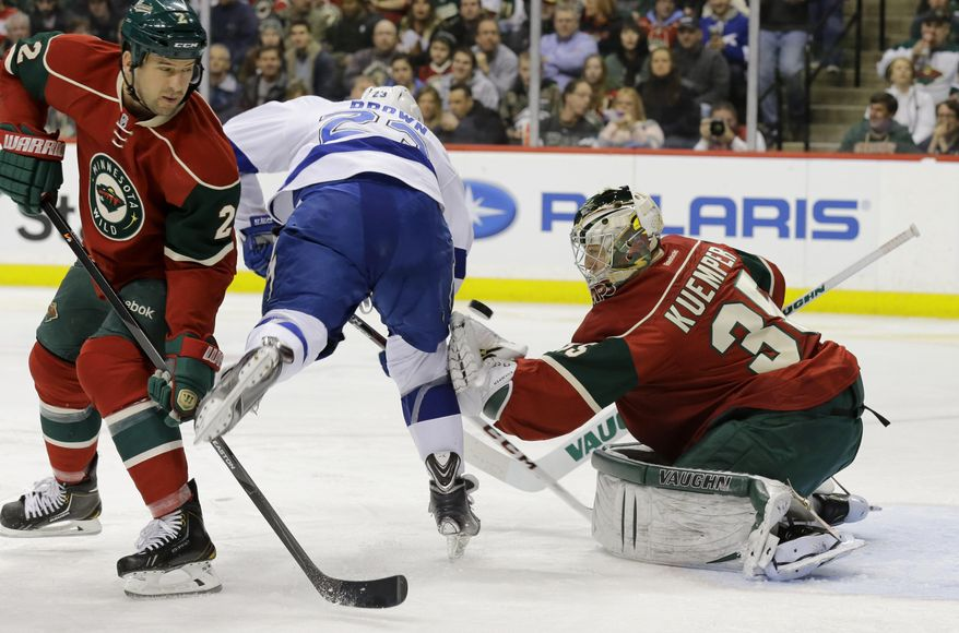 Minnesota Wild goalie Darcy Kuemper (35) deflects a shot by Tampa Bay Lightning right wing J.T. Brown (23) as Wild's Keith Ballard, left, defends during the second period of an NHL hockey game in St. Paul, Minn., Tuesday, Feb. 4, 2014. (AP Photo/Ann Heisenfelt)