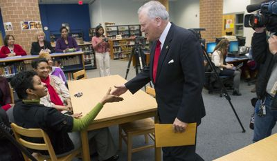 Georgia Governor Nathan Deal, right,  greets math teacher Nicole Brown Tuesday, Feb. 4, 2014, in Atlanta during a visit to Westlake High School to thank faculty and staff for keeping students safe during last week's snow storm. Brown was one of the 450 people stranded at the school during the storm and spent much of the time fielding phone calls from parents worried about their children. (AP Photo/John Amis)