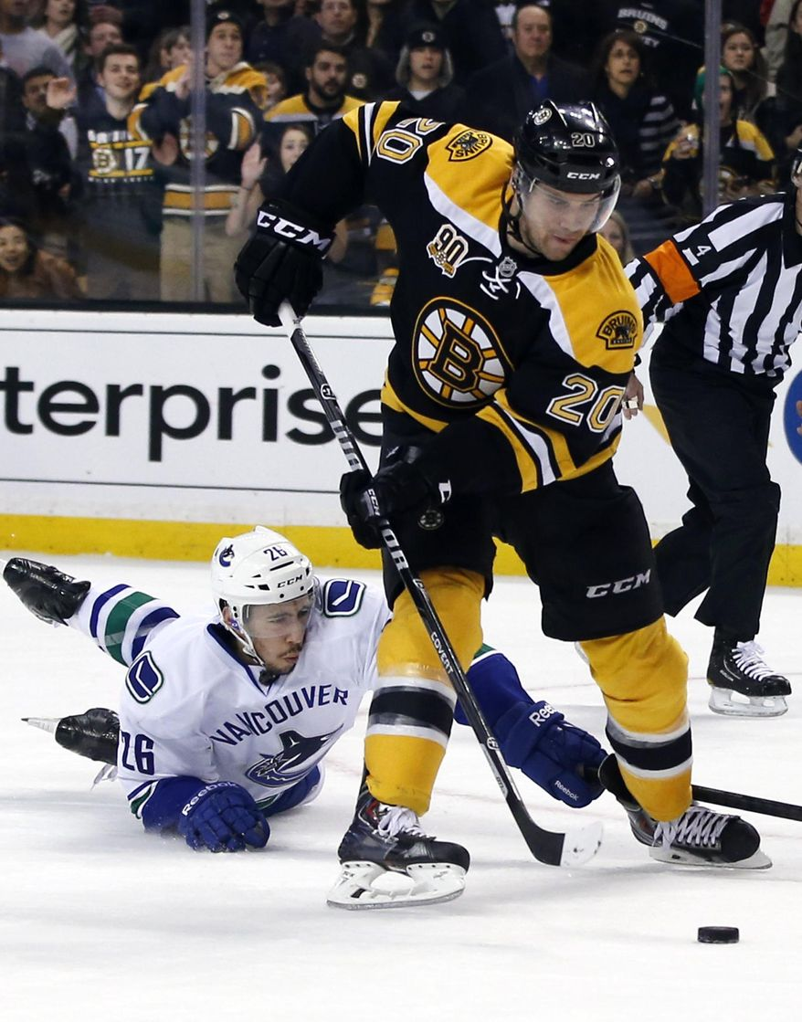 Boston Bruins left wing Daniel Paille (20) shoots and scores on a breakaway as Vancouver Canucks defenseman Frank Corrado (26) tries to stop him during the second period of an NHL hockey game in Boston on Tuesday, Feb. 4, 2014. (AP Photo/Elise Amendola)