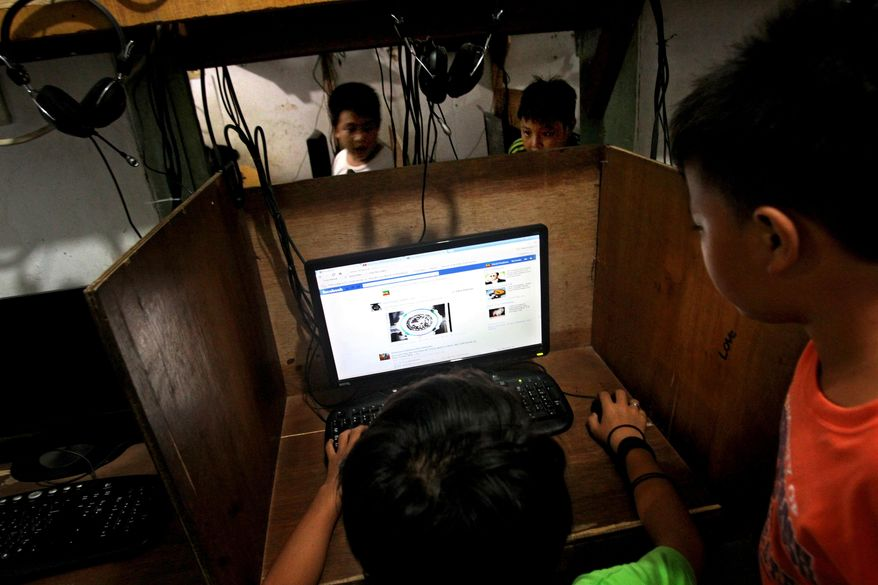 ** FILE ** In this June 19, 2013, file photo, an Indonesian youth browses his Facebook page at an Internet cafe in Jakarta, Indonesia. (AP Photo/Tatan Syuflana, File)