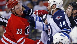 Carolina Hurricanes' Alexander Semin (28) of Russia, and Winnipeg Jets' Zach Bogosian (44) scuffle in front of the net during the second period of an NHL hockey game in Raleigh, N.C., Tuesday, Feb. 4, 2014. (AP Photo/Karl B DeBlaker)