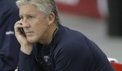 **FILE** Seattle Seahawks head coach Pete Carroll, front, and his brother, Jim Carroll, talk on their phones prior to an NFL football game against the Arizona Cardinals Sunday, Nov. 14, 2010, in Glendale, Ariz. (AP Photo/Ralph Freso)