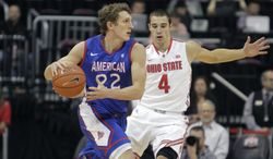 "FILE - This Nov. 20, 2103 file photo shows American University's John Schoof, left, guarded by Ohio State's Aaron Craft during the first half of an NCAA college basketball game in Columbus, Ohio. From Princeton to American by way of Georgetown with a guard named ""Peewee,"" Mike Brennan has the Eagles unbeaten in the Patriot League in his first season at the school.  (AP Photo/Jay LaPrete, File)"