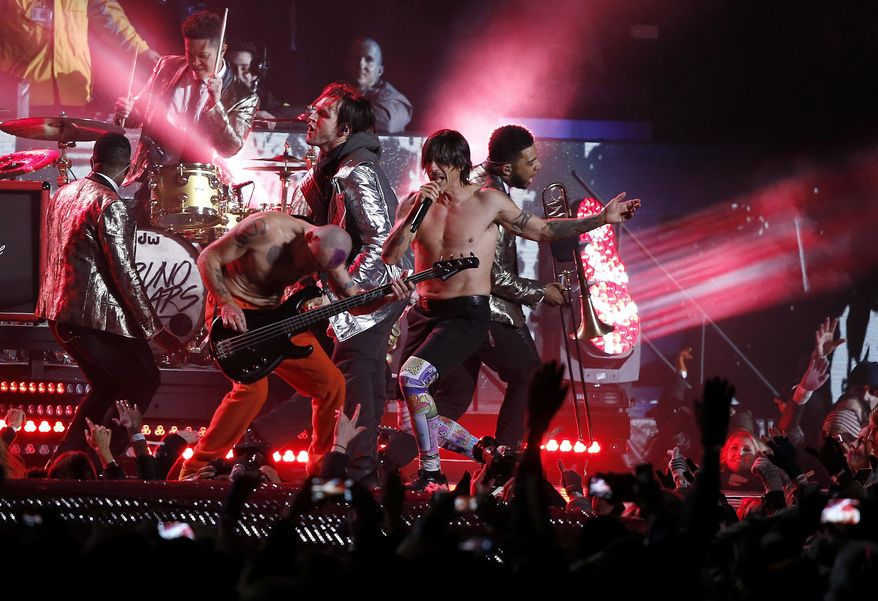 """FILE - In this Sunday, Feb. 2, 2014 file photo, The Red Hot Chili Peppers perform during the halftime show of the NFL Super Bowl XLVIII football game between the Seattle Seahawks and the Denver Broncos, in East Rutherford, N.J. Flea says in a Tuesday, Feb. 4, 2014, letter to fans that the Rock and Roll Hall of Fame members pretended to play along to a pre-taped track of """"Give It Away"""" during the Super Bowl halftime show as Anthony Kiedis sang live. The request came from NFL officials who felt it was too difficult to pull off a completely live performance because of potential sound issues. (AP Photo/Kathy Willens, File)"""