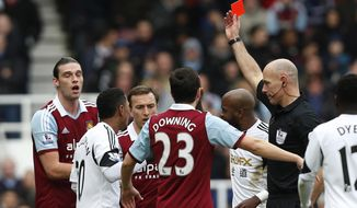West Ham United's Andy Carroll, left, is shown a red card by referee Howard Webb for his challenge on Swansea City's Chico Flores during their English Premier League soccer match at Upton Park, London, Saturday, Feb. 1, 2014. (AP Photo/Sang Tan)