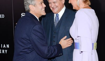 "Director and actor George Clooney, left, greets actor Hugh Bonneville and his wife Lulu on the red carpet at the premiere of ""The Monuments Men"" at the Ziegfeld Theatre on Tuesday, Feb. 4, 2014, in New York.  (Photo by Evan Agostini/Invision/AP)"