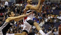 Washington Wizards guard Garrett Temple (17) drives past San Antonio Spurs guard Marco Belinelli (3), from Italy, in the first half of an NBA basketball game on Wednesday, Feb. 5, 2014, in Washington. (AP Photo/Alex Brandon)